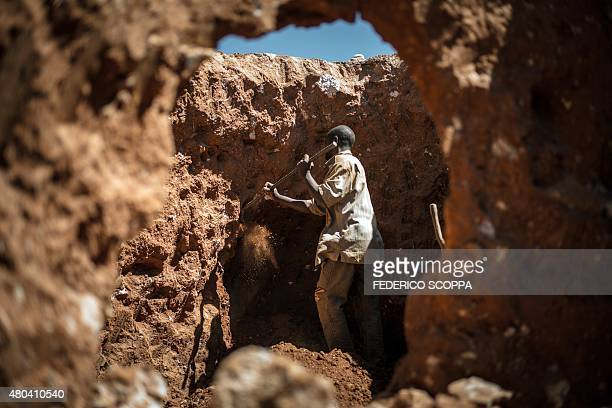 This photo taken on May 31 2015 between Lubumbashi and Kolwezi shows a man digging through some mine waste searching for left over cobalt one of...