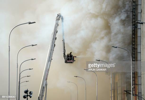 This photo taken on May 31 2017 shows Indian firefighters spraying water to control a fire amid billowing smoke at a garment shop in Chennai No major...