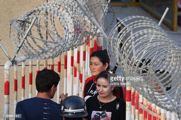 This photo taken on May 31 2019 shows a Uighur woman going through an entrance to a bazaar in Hotan in China's northwest Xinjiang region A recurrence...