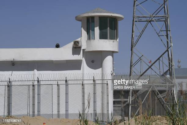 This photo taken on May 31 2019 shows a watchtower on a highsecurity facility near what is believed to be a reeducation camp where mostly Muslim...