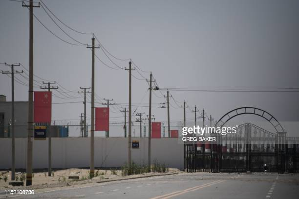 This photo taken on May 31 2019 shows Chinese flags on a road leading to a facility believed to be a reeducation camp where mostly Muslim ethnic...