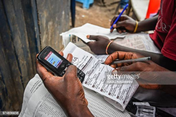 This photo taken on May 6 2018 shows a man betting on European football games with a mobile phone at sports betting shop in Kampala Uganda On a dark...