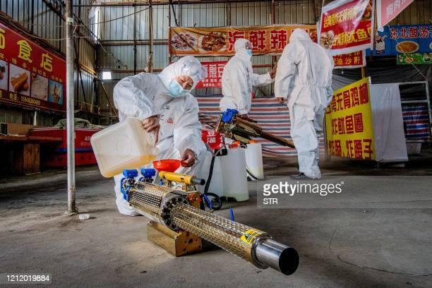 This photo taken on May 6 2020 shows a volunteer filling a sprayer with disinfectant at a market as a preventive measure against the COVID19...