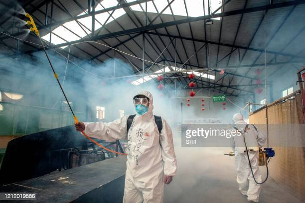 This photo taken on May 6 2020 shows volunteers spraying disinfectant at a market as a preventive measure against the COVID19 coronavirus as it...