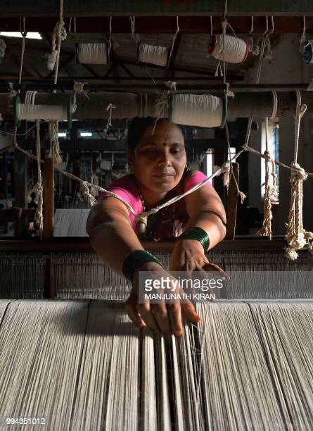 This photo taken on May 9 2018 shows an employee of Khadi Gramodyog Samyukta Sangh weaving cotton fibre to be later used to make the Indian national...