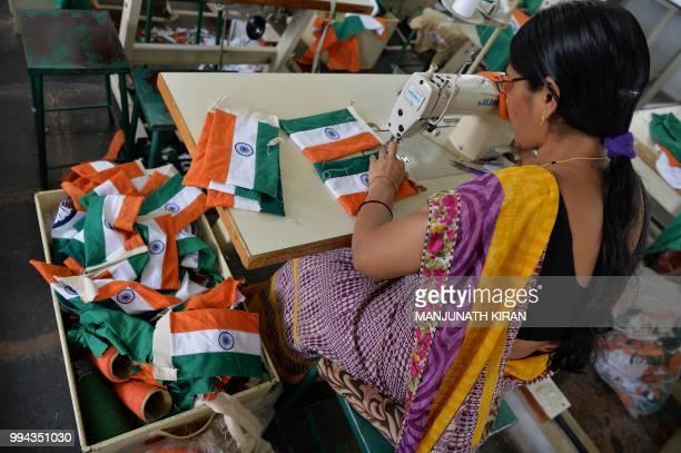 This photo taken on May 9 2018 shows an employee of Khadi Gramodyog Samyukta Sangh stitching together an Indian national flag at the Indian National...