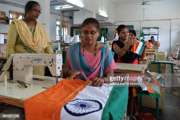 This photo taken on May 9 2018 shows employees of Khadi Gramodyog Samyukta Sangh stitching together an Indian national flag at the Indian National...