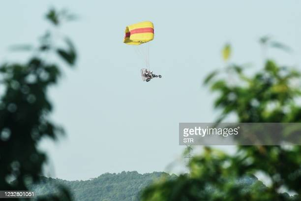 This photo taken on May 9, 2021 shows a rescuer taking a powered parachute as he searches leopards which escaped from a wild park in Hangzhou, in...