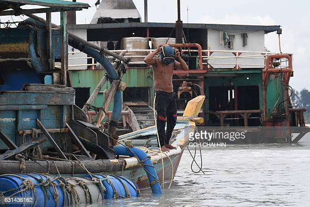 This photo taken on November 10 2016 shows illegal miner Paci adjusting his mask as he prepares for a dive to dredge tin from the seabed off Sungai...