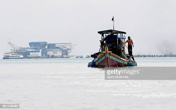 This photo taken on November 10 2016 shows illegal miner Paci on his boat after a dive where he dredged for tin from the seabed off Sungai Liat in...