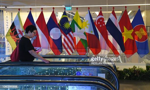 This photo taken on November 10, 2018 shows a woman walking past the national flags of Association of Southeast Asian Nations countries at the Suntec...