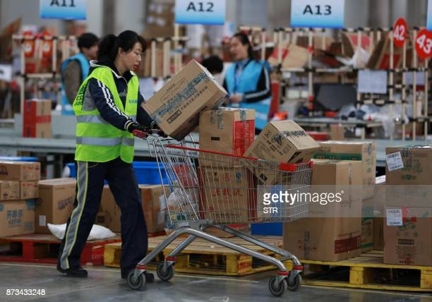 This photo taken on November 11 2017 shows a staff member of a delivery company carrying boxes during the 'Singles Day' shopping festival in Shenyang...