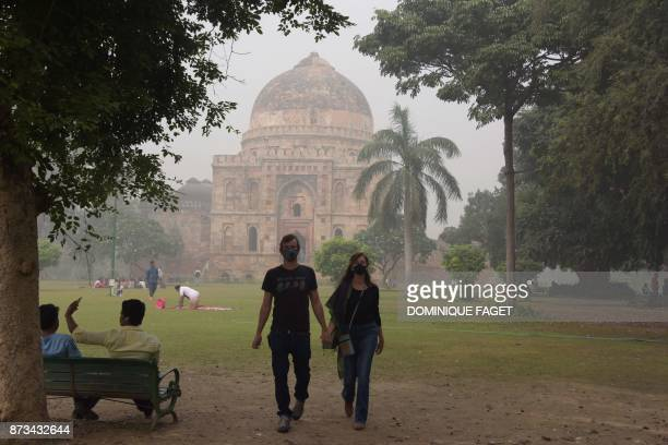 This photo taken on November 12 2017 shows tourists visiting Lodi Gardens amid heavy smog in New Delhi Schools reopened in New Delhi on November 13...