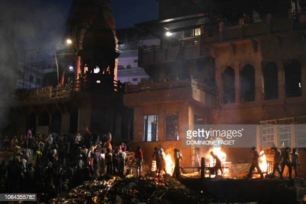 This photo taken on November 13, 2018 shows bodies being cremated at the traditional crematorium grounds at Manikarnika Ghat on the Ganges river in...