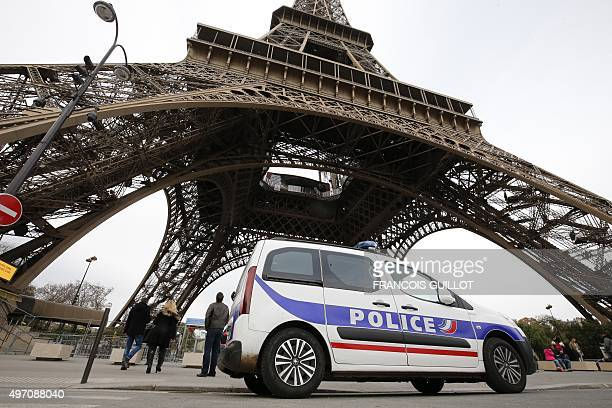This photo taken on November 14 2015 shows a police car stationed next to the Eiffel Tower in Paris European capitals reinforced security checks as...