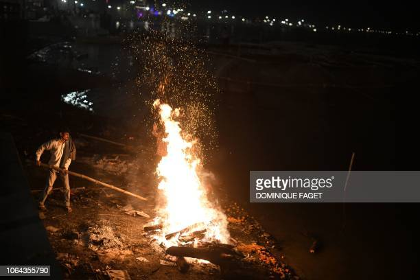 This photo taken on November 14, 2018 shows an Indian man stoking a funeral pyre at the traditional crematorium grounds at Harischandra Ghat on the...