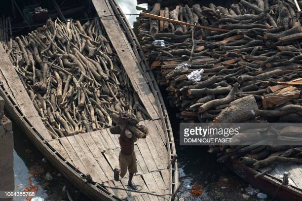 This photo taken on November 14, 2018 shows an Indian worker unloading wood from a boat to be used at the traditional crematorium grounds at...