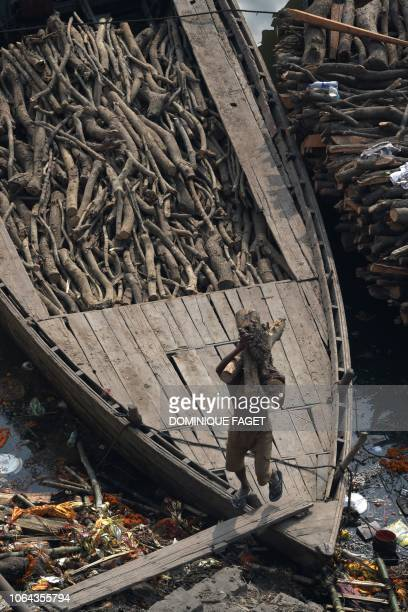 This photo taken on November 14 2018 shows an Indian worker unloading wood from a boat to be used at the traditional crematorium grounds at...