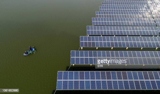 This photo taken on November 14 2018 shows Chinese fishermen next to a photovoltaic power station built on top of fish ponds in Yangzhou in China's...