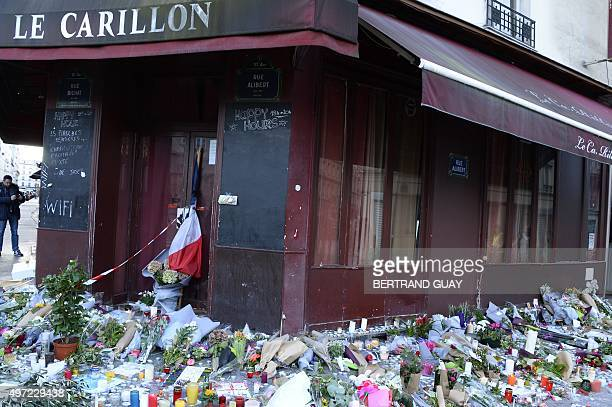 This photo taken on November 15 2015 shows flowers notes and candles at a memorial site outside of the Carillon bar in the 10th district of Paris for...