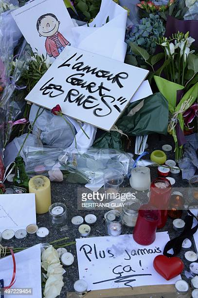 This photo taken on November 15, 2015 shows flowers, notes and candles at a memorial site outside of the Carillon bar, in the 10th district of Paris,...