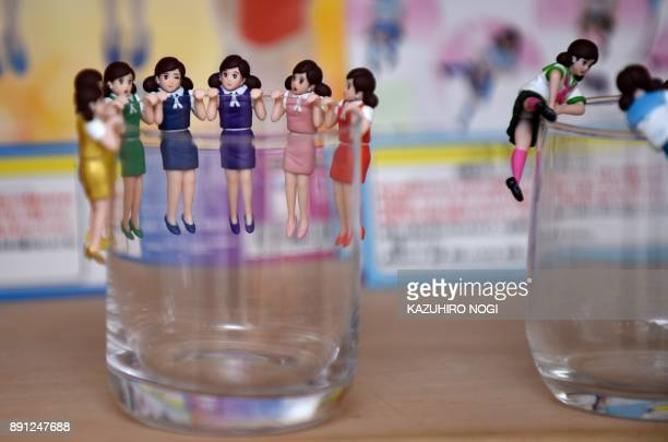 This photo taken on November 15 2017 shows figurines of women wearing typical office clothes whose arms or legs are designed to hang over the edge of...