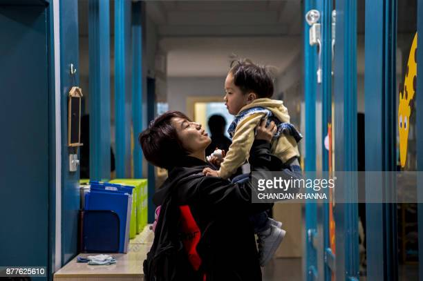 This photo taken on November 16 2017 shows MMA fighter Miao Jie saying goodbye as she drops her threeyearold son Li Muyuan off at school in Shanghai...