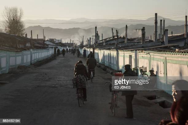 TOPSHOT This photo taken on November 19 2017 shows cyclists passing along a road on the outskirts of the industrial city of Chongjin on North Korea's...
