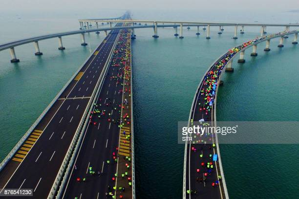 TOPSHOT This photo taken on November 19 2017 shows participants crossing the Jiaozhou Bay Bridge as they compete in the 2017 Qingdao International...