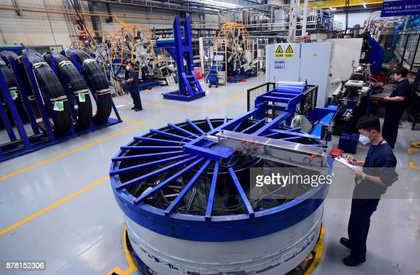 This photo taken on November 22 2017 shows employees working on a production line of automobiles at the BMW factory in Shenyang in China's...