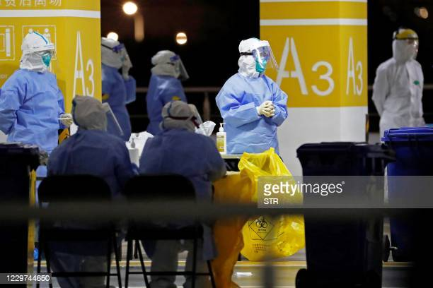 This photo taken on November 22, 2020 shows health workers in protective suits waiting to conduct COVID-19 coronavirus tests on staff at Pudong...