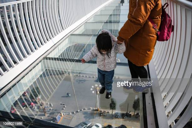 This photo taken on November 24, 2018 shows people walking on a glass bridge in Shijiazhuang, in China's northern Hebei province. - The bridge, which...