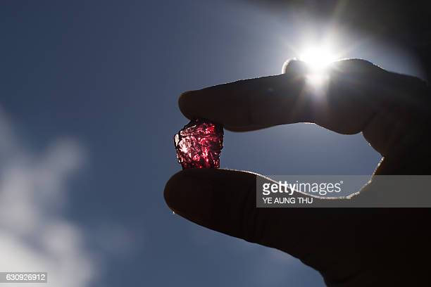 This photo taken on November 25 2016 shows a buyer checking a ruby in the gems market in Mogok north of Mandalay Myanmar produces more than 80...