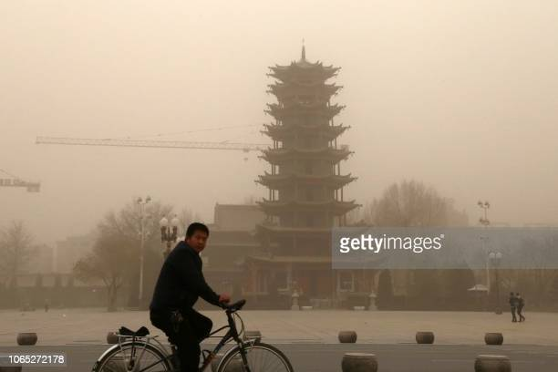 TOPSHOT This photo taken on November 25 2018 shows a cyclist riding in a sandstorm in Zhangye in China's northwestern Gansu province A northwest...