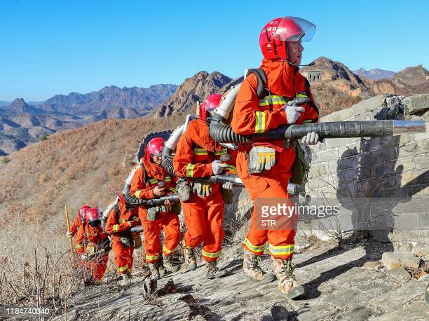 This photo taken on November 25, 2019 shows fire fighters patroling along a part of the Great Wall in Qinhuangdao, in China's northern Hebei...