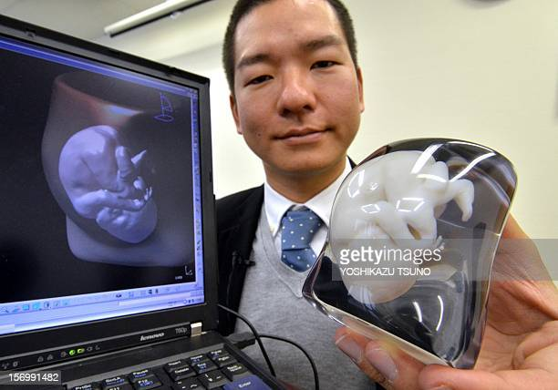 This photo taken on November 26 2012 shows Japan's 3D computeraided design venture Fasotec employee Tomohiro Kinoshita displaying a ninemonth fetus...