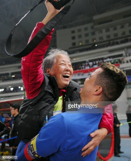 This photo taken on November 26 2017 shows Shanghai Shenhua's Giovanni Moreno lifting up photographer Hong Nanli after the Chinese FA football match...