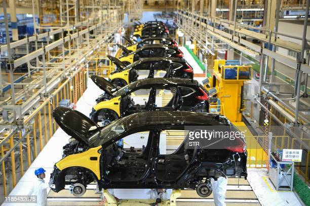 This photo taken on November 27 2019 shows employees working on an assembly line at the third auto plant of Dongfeng Honda in Wuhan in China's...