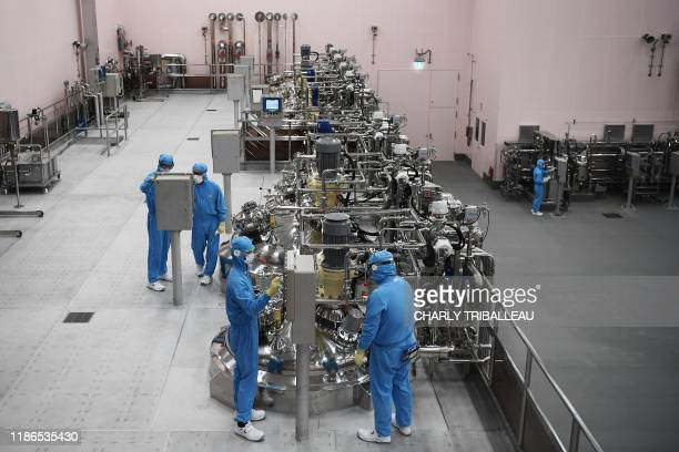 This photo taken on November 27, 2019 shows workers at the inauguration of a new production plant for Japanese cosmetics brand Shiseido in Otawara,...
