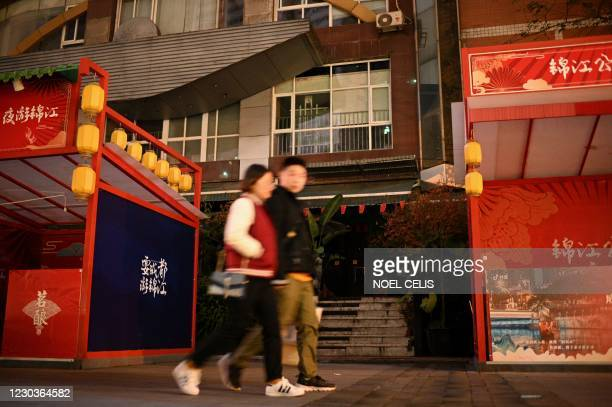 This photo taken on November 27, 2020 shows people walking in front of the closed gay sauna MC Club in Chengdu, the capital of southwest Sichuan...