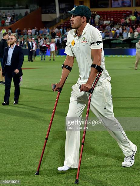This photo taken on November 29 2015 show Australia's pace spearhead Mitchell Starc walking onto the field with crutches at the end of first daynight...
