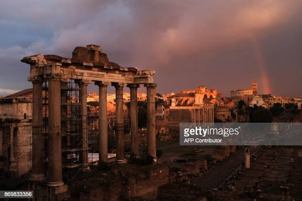This photo taken on November 3, 2017 in Rome shows a rainbow over the ruins of the ancient Roman Forum during a sunset. / AFP PHOTO / Alberto PIZZOLI