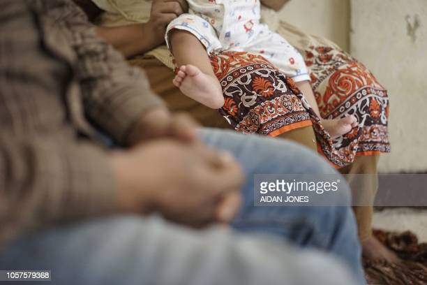 This photo taken on November 3 2018 shows family members of PakistaniChristian refugees seeking refuge in a small apartment in Bangkok suburb after...