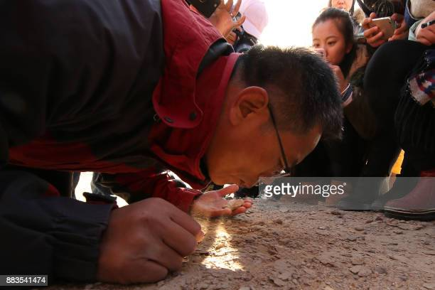 This photo taken on November 30, 2017 shows Chinese scientist Wang Xiaolin investigating the ground in Hami, in northwestern China's Xinjiang Region....