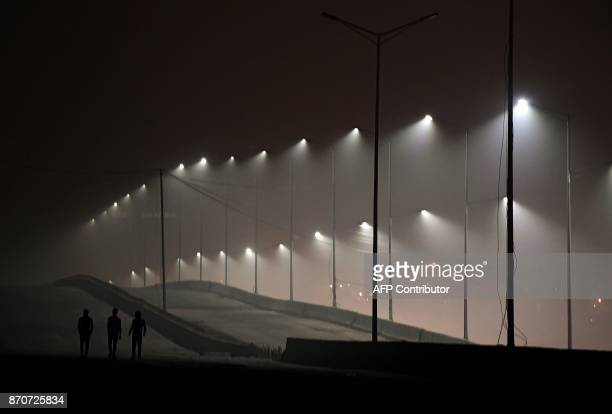 This photo taken on November 5 2017 shows people walking on an underconstruction flyover as smog covers the capital's skyline in New Delhi / AFP...