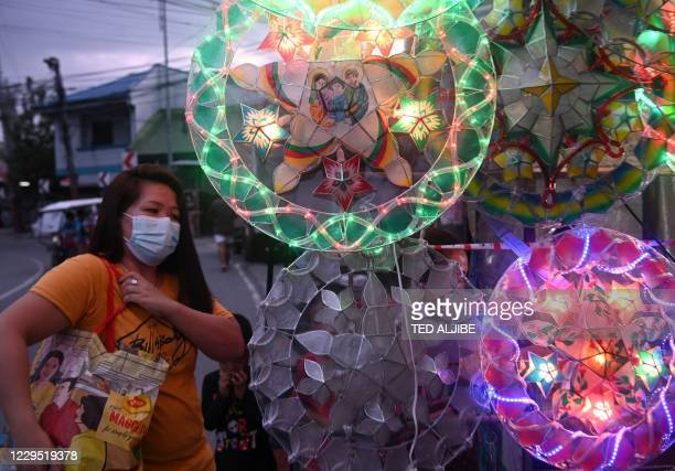 This photo taken on November 5, 2020 shows a woman wearing a mask to protect herself from the Covid-19 coronavirus, stands next to giant lanterns for...