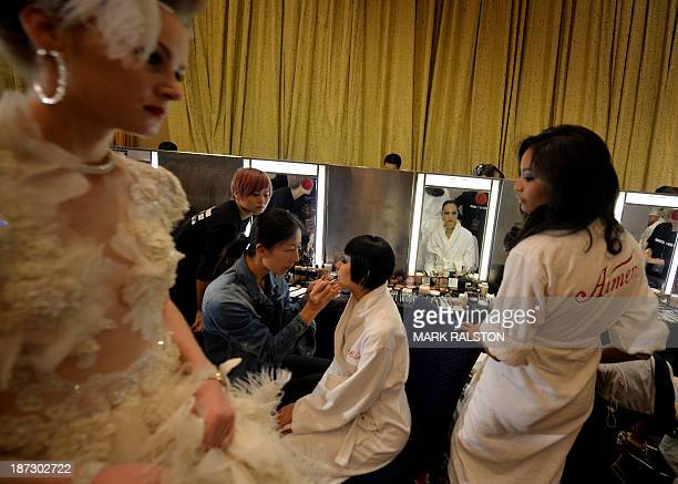 This photo taken on November 7 2013 shows Chinese models and foreign performers preparing backstage before filming the lingerie section of the...