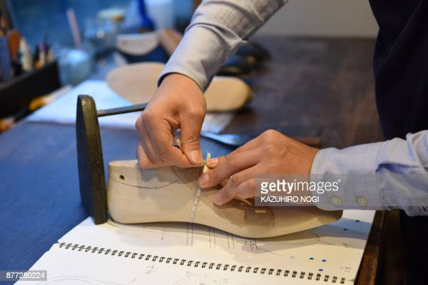 This photo taken on November 7 2017 shows Japanese master shoemaker Yohei Fukuda working in his workshop in Tokyo When Yohei Fukuda left for England...