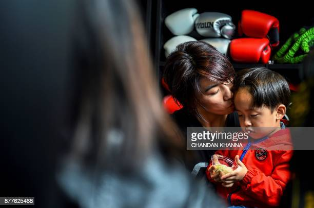 This photo taken on November 7 2017 shows MMA fighter Miao Jie with her son Li Muyuan during a break in a training session in Shanghai The 30yearold...