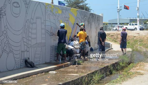 This photo taken on November 7 2018 shows local workers painting a mural on a wall in Port Moresby the host city for the upcoming AsiaPacific...